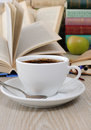 A cup of coffee on a table among books the against the background an open book with notebook Royalty Free Stock Image