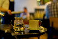 Cup of coffee or tee, glass teapot of hot water, morning. Image with blurred cafe visitors and a waiter in a low key Royalty Free Stock Photo