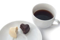 Cup of coffee and two heart-shaped chocolates on plate. Royalty Free Stock Photo