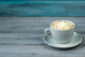 Cup of coffee with whipped cream on wooden background Royalty Free Stock Photo