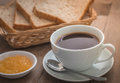 Cup of coffee with whole wheat bread in basket and jam Royalty Free Stock Photo