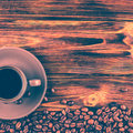 A cup of coffee on a wooden background.