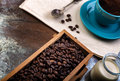 Cup of coffee and wooden containers filled with cofee beans on the rust background cane sugar low light Stock Images