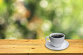 Cup of coffee on the wooden floor and bokeh background Royalty Free Stock Photo