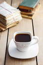 Cup of coffee on wooden table. Vintage books and pile of letters