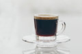 Cup of delicious frothy black espresso coffee freshly brewed full roast served in a glass mug and saucer on a reflective grey Stock Photos