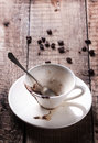 Cup of drunk coffee with ground on old wooden table with beans Royalty Free Stock Photos