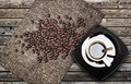 Cup of espresso coffee with beans and canvas on weathered wooden table Stock Photos