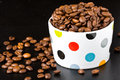 Cup filled with coffee beans colored polka dots whole on a black background Stock Photos