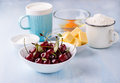 Cup of flour, butter, cherry, egg and milk Royalty Free Stock Photo