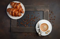 Cup of fresh coffee with croissants on dark background Royalty Free Stock Photo