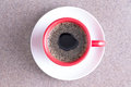 Cup of fresh energising black coffee poured into a red on a white saucer centered over a grey cloth background Royalty Free Stock Images
