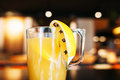 Cup of fresh orange juice at bar close up mug with tasty appetizing yellow citrus drink with cloves blurred saloon background Royalty Free Stock Photography