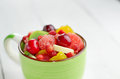 Cup with fruits ceramic mixed fruit salad on the white table Royalty Free Stock Photo