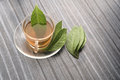 A cup of Green tea and leafs decoreted nicely on wood talbe Royalty Free Stock Photo