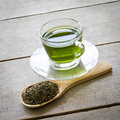 Cup of green tea and spoon of dried green tea leaves on wooden background Stock Photography