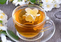 Cup of herbal tea with jasmine flowers on wooden table Stock Images
