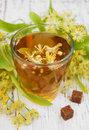 Cup of herbal tea with linden flowers on a old wooden background Royalty Free Stock Photo