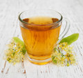 Cup of herbal tea with linden flowers on a old wooden background Royalty Free Stock Images