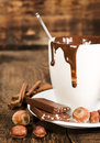 Cup of hot chocolate with nuts and cinnamon close up on wooden background Royalty Free Stock Photo