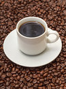 Cup with Hot Coffee on Coffee Beans Stock Photos