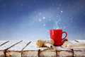 Cup of hot coffee and cozy knitted scarf on wooden