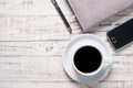 Cup of hot coffee and white note book on wood table background Royalty Free Stock Images