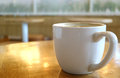 Cup of Hot Coffee on a Wooden Table with Sunlight Reflections Royalty Free Stock Photo