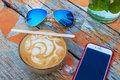 Cup of hot espresso coffee drink with sunglasses and mobile phone