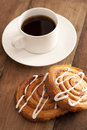 Cup of hot espresso coffee with fresh buns spiral decorated vanilla icing served on a wooden counter top Stock Image