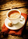 Cup of hot frothy espresso coffee served on a rustic cloth with a small macaroon in a rural country cafeteria on a weathered wood Royalty Free Stock Photo
