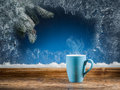 Cup of hot tea, frozen window and Christmas tree. Royalty Free Stock Photo