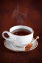 Cup of hot tea and rock candy sugar stick selective focus Stock Photo