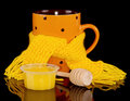 Cup of hot tea in scarf with honey isolated on black Royalty Free Stock Photo