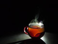 Cup of hot tea with steam shining with different colors Royalty Free Stock Image