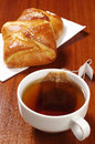 Cup of hot tea with teabag and sweet buns on table Stock Photography