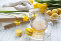 A cup of hot tea, yellow tulips, yellow daffodils, old books and lemon macaroons on a light background