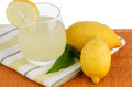 Cup of lemon juice and fresh lemons Royalty Free Stock Image