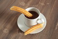 Cup of liquid chocolate and churros on a wooden table Stock Photography