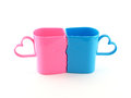 closeup two colorful (pastel pink and blue) plastic cups shaped faces of men and women were kissing with heart shape Royalty Free Stock Photo