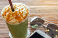 Cup of the matcha greentea frappe with caramel whipped cream on the brown bark beautiful texture background with warm light Royalty Free Stock Photo