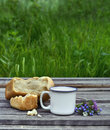 Cup of milk with bread and flower bunch Royalty Free Stock Photo