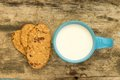 Cup of milk with cookies for healthy breakfast blue on wooden table Royalty Free Stock Photography