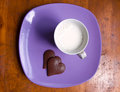 Cup of milk and heart shaped chocolate on plate a a purple with wooden table Royalty Free Stock Photography