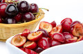 Cup of pitted cherries and whole cherries in a basket isolated on white Royalty Free Stock Image