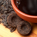 The cup of pu-erh and two bricks of tea Stock Photo