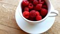 Cup with raspberries white coffee filled Stock Image