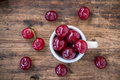 Cup with ripe cherries on the old wooden background rustic Royalty Free Stock Photos
