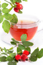Cup of rose hip tea and berries over white Royalty Free Stock Photography