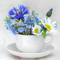 Cup and saucer with bunch of wild flowers Royalty Free Stock Photo